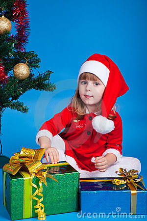 Pretty baby miss Santa sitting near Christmas tree