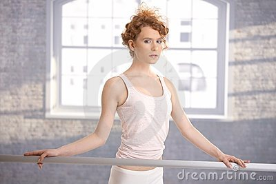 Pretty ballerina girl standing by bar practicing