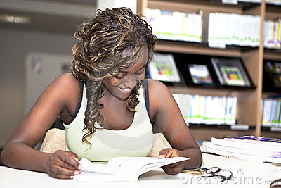 Pretty black african student girl reading books