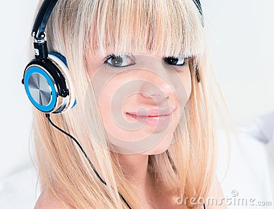 Pretty blond girl listening to music on her smartphone