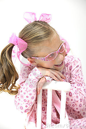 Pretty blond girl with pink glasses sitting on a c
