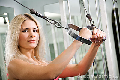 Pretty blond woman exercising on pulldown station