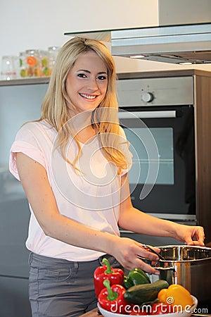 Pretty blond woman preparing a meal