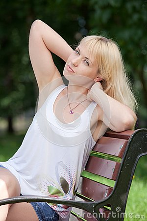 Pretty  blond woman sits with raised arms on park