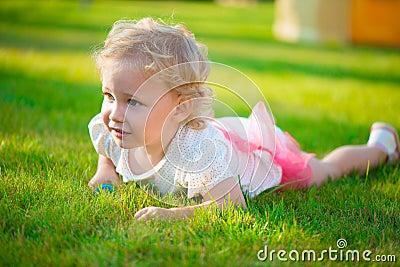 Pretty blonde girl lying on grass