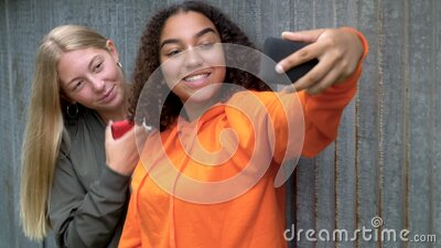 Pretty blonde girl and mixed race teenager young women taking selfies on their smart phones for social media stock video