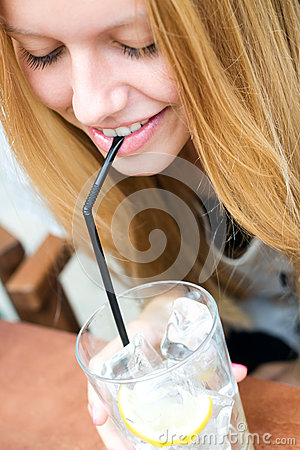 Pretty blonde girl taking a drink on a terrace