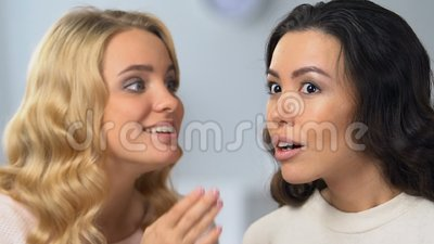 Pretty blonde girl whispering secrets to her attractive asian friend, gossips. Stock footage stock footage