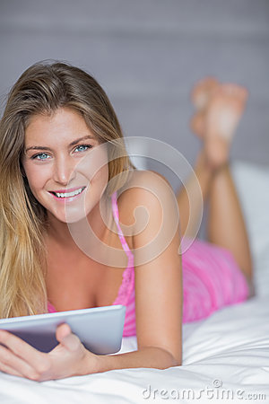 Pretty blonde lying on her bed using her tablet pc