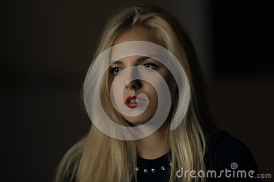 Pretty blonde bewildered in the dark Stock Photo