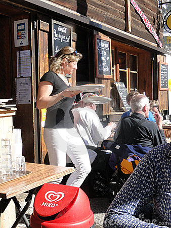 A pretty blonde waitress serves lunch outdoors Editorial Stock Photo