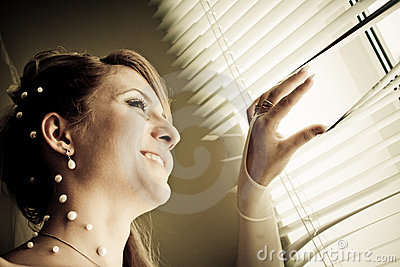 Pretty bride looking out of window
