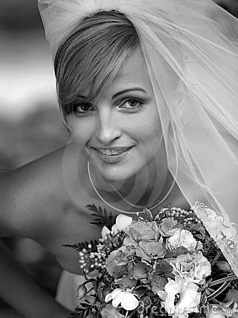 In black and white portrait with traditional wedding dress and veil