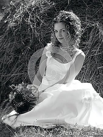 Pretty bride sat in field