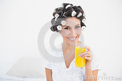 Pretty brunette in hair rollers holding glass of orange juice sm