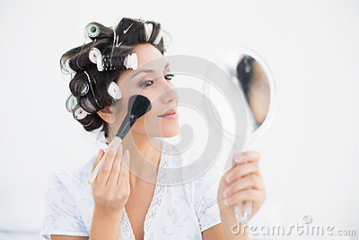 Pretty brunette in hair rollers holding hand mirror and applying