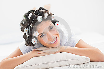 Pretty brunette in hair rollers lying on her bed smiling at camera