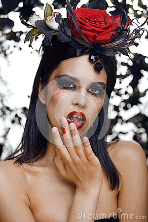 Pretty brunette woman with rose jewelry, black and red, bright make up kike a vampire