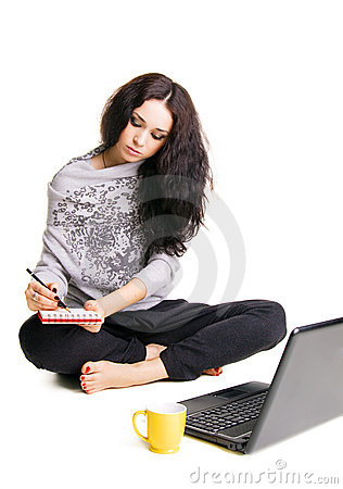 Pretty brunette working with laptop and notebook