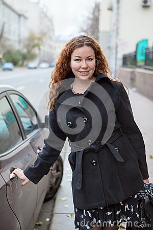 Pretty business woman standing near the vehicle