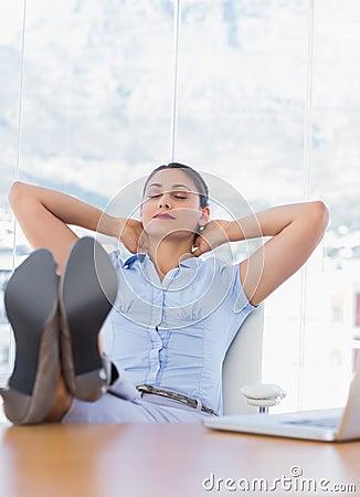 Pretty businesswoman relaxing in her office