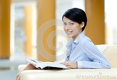 Pretty businesswoman rests at the sofa with book