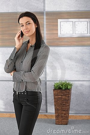 Pretty businesswoman talking on mobile smiling Stock Photo