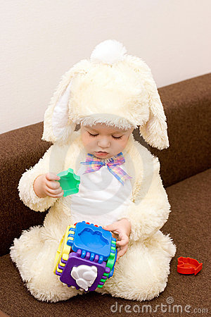 Pretty caucasian baby in rabbit costume playing
