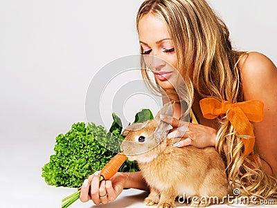 Pretty cheerful girl feeding a rabbit