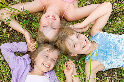 Pretty children and teenager girls on green grass