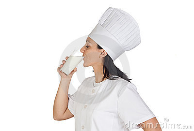 Pretty cook girl drinking milk