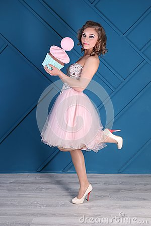 Free Pretty Curly Woman In Pink Dress And Heels Holds Cupcake Stock Image - 99739681