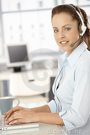 Pretty dispatcher working in bright office smiling