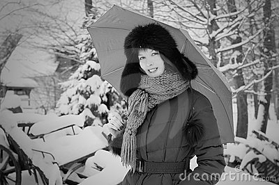 Pretty elegant woman in winter with umbrella