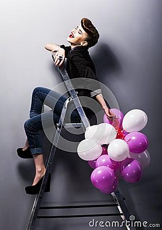 Pretty fashion retro teen girl laughing on ladder