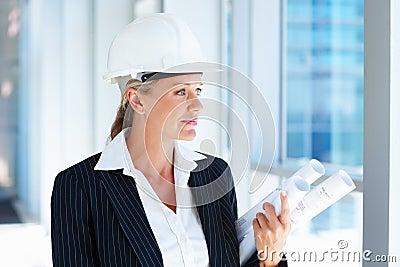 A pretty female architect holding blueprints