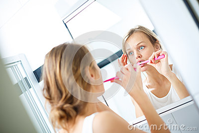 Pretty female brushing her teeth in front of mirror