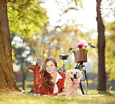 Pretty female lying down with labrador retriever dog in a park