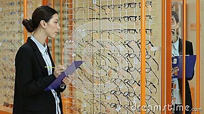 Pretty female optician revising glasses in optics stock video footage
