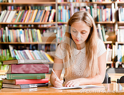 Pretty female student with books working in a high school library Stock Photo