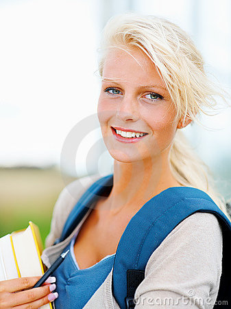 Pretty female student holding books , outdoors