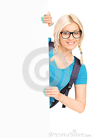 Pretty female student posing behind white panel