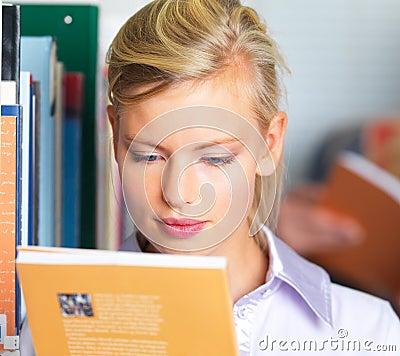 Pretty female student reading a book
