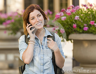 Pretty Female Student Walking Outside Using Cell Phone