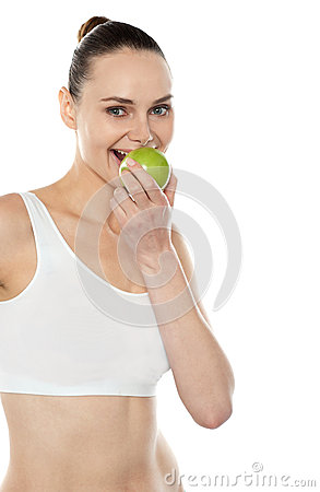 Pretty fit trendy woman eating fresh green apple