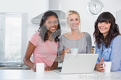 Pretty friends having coffee together with laptop