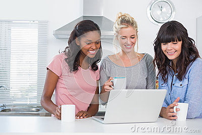 Pretty friends having coffee together and looking at laptop