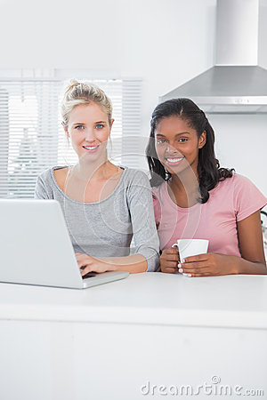 Pretty friends using laptop together and smiling at camera