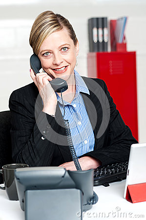 Pretty front desk lady attending clients call