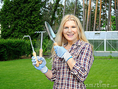 Pretty gardener woman with gardening tools